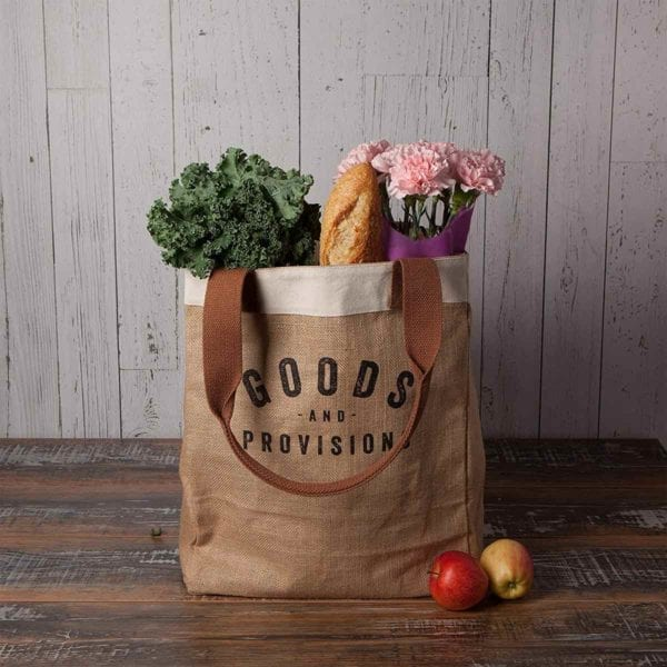 Burlap Market Tote filled with groceries on wooden table.