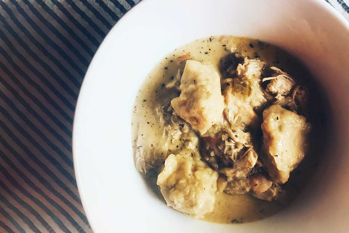 A white bowl filled with chicken and dumplings.