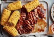 A tray of chicken thighs with balsamic barbecue sauce, corn on the cob, glasses of beer, forks, and plates
