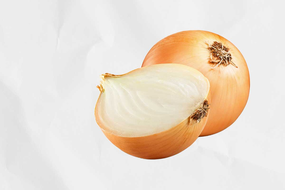 A whole onion and a cut onion half which you can use if you want to know how to clean your grill.