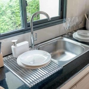Foldable Multi-Use Drying Mat on sink with plates.
