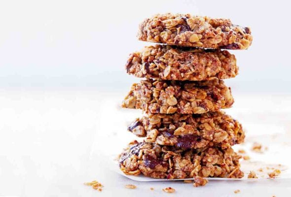A stack of gluten-free vegan oatmeal cookies with chocolate on a white sheet.