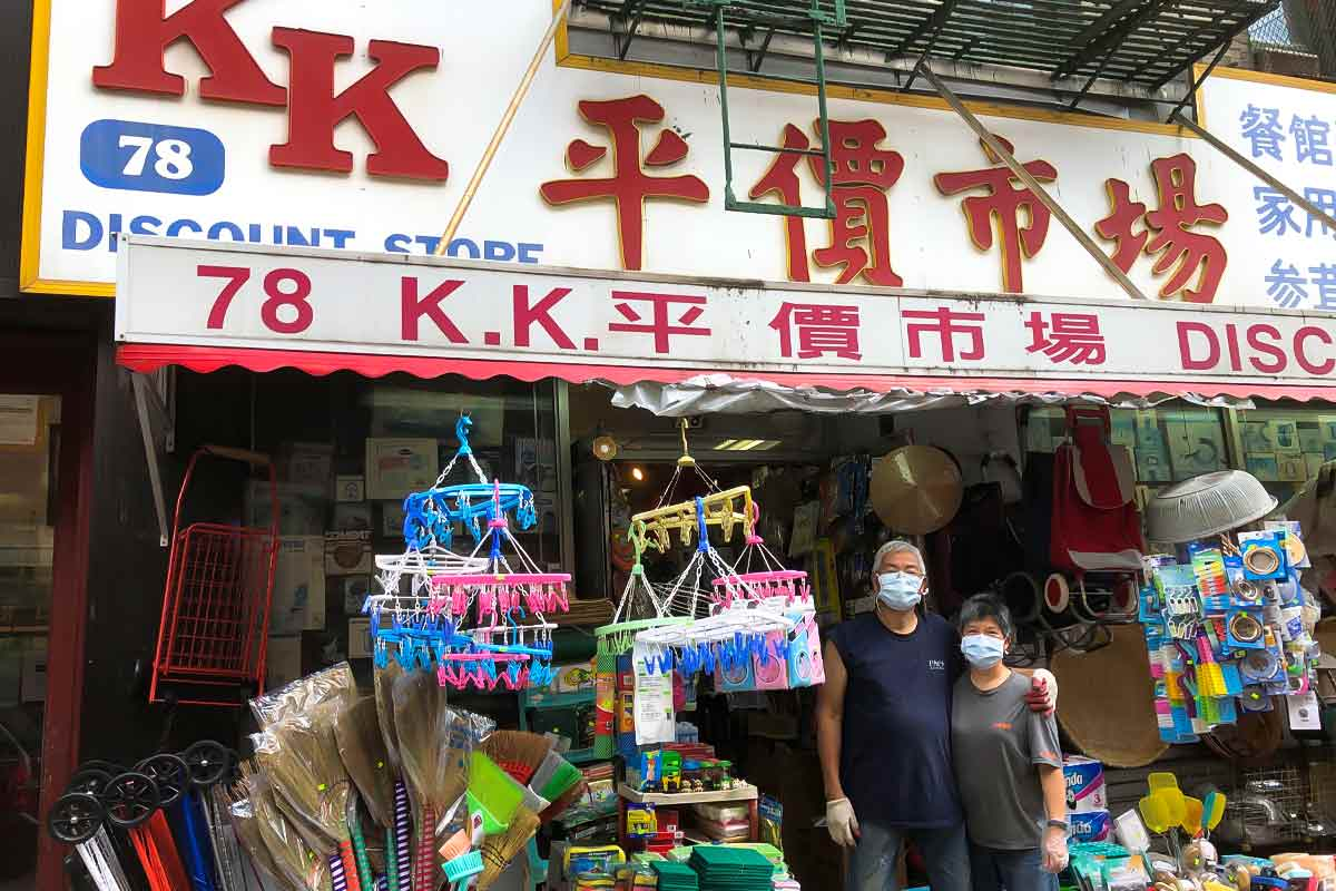 The owners posing in front of the KK Discount Store for the podcast Ep. 31: Grace Young: Coronavirus: Chinatown Stories.