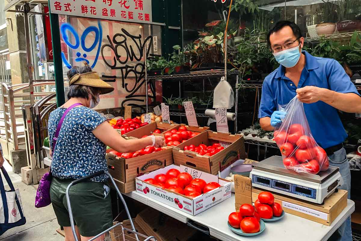 An Asian man with a mask bagging tomatoes and a woman shopping for tomatoes for the podcast Ep. 31: Grace Young: Coronavirus: Chinatown Stories.