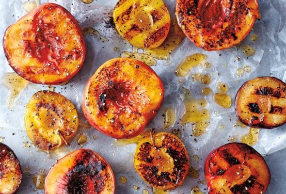 Grilled peaches with honey and black pepper scattered on a piece of parchment paper.
