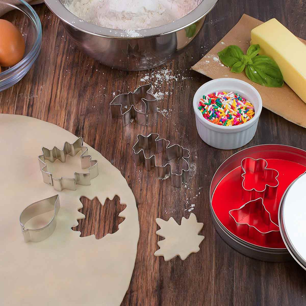 Leaf Shape Cookie Cutters on table with dough and sprinkles.