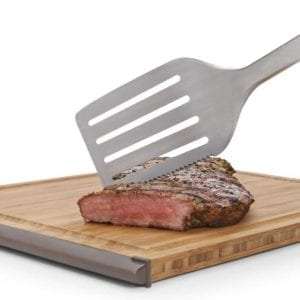 A spatula from an OXO good grips 2-piece grilling set cutting into a steak on a wooden board.