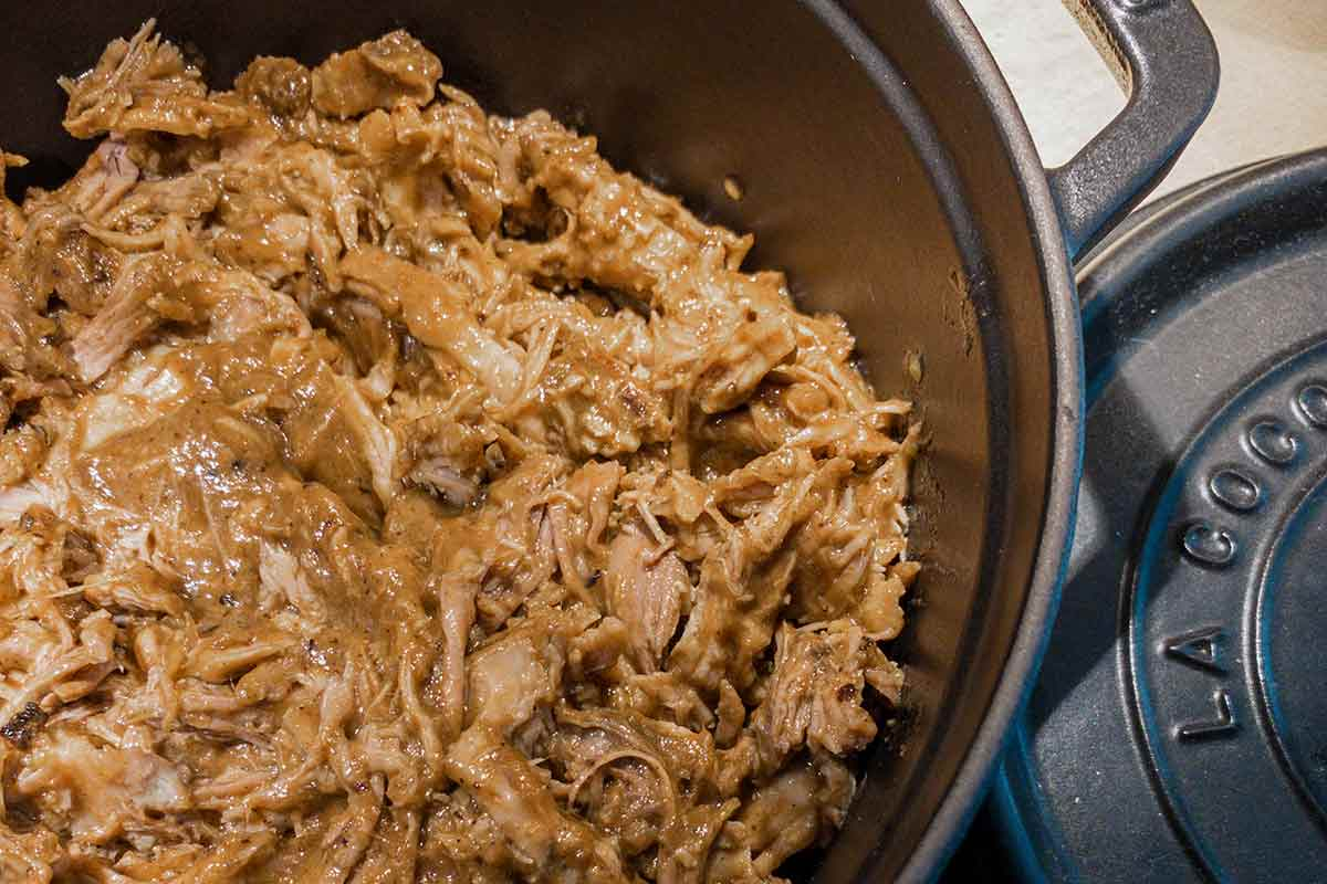 A cast-iron pot filled with pulled pork for pulled pork tacos.