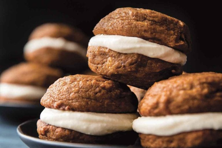 Two plates each with four pumpkin spice whoopie pies with cream cheese filling stacked on them.