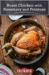 A whole roast chicken with rosemary and potatoes on a wooden table with four plates and a tray of roasted plums beside it.