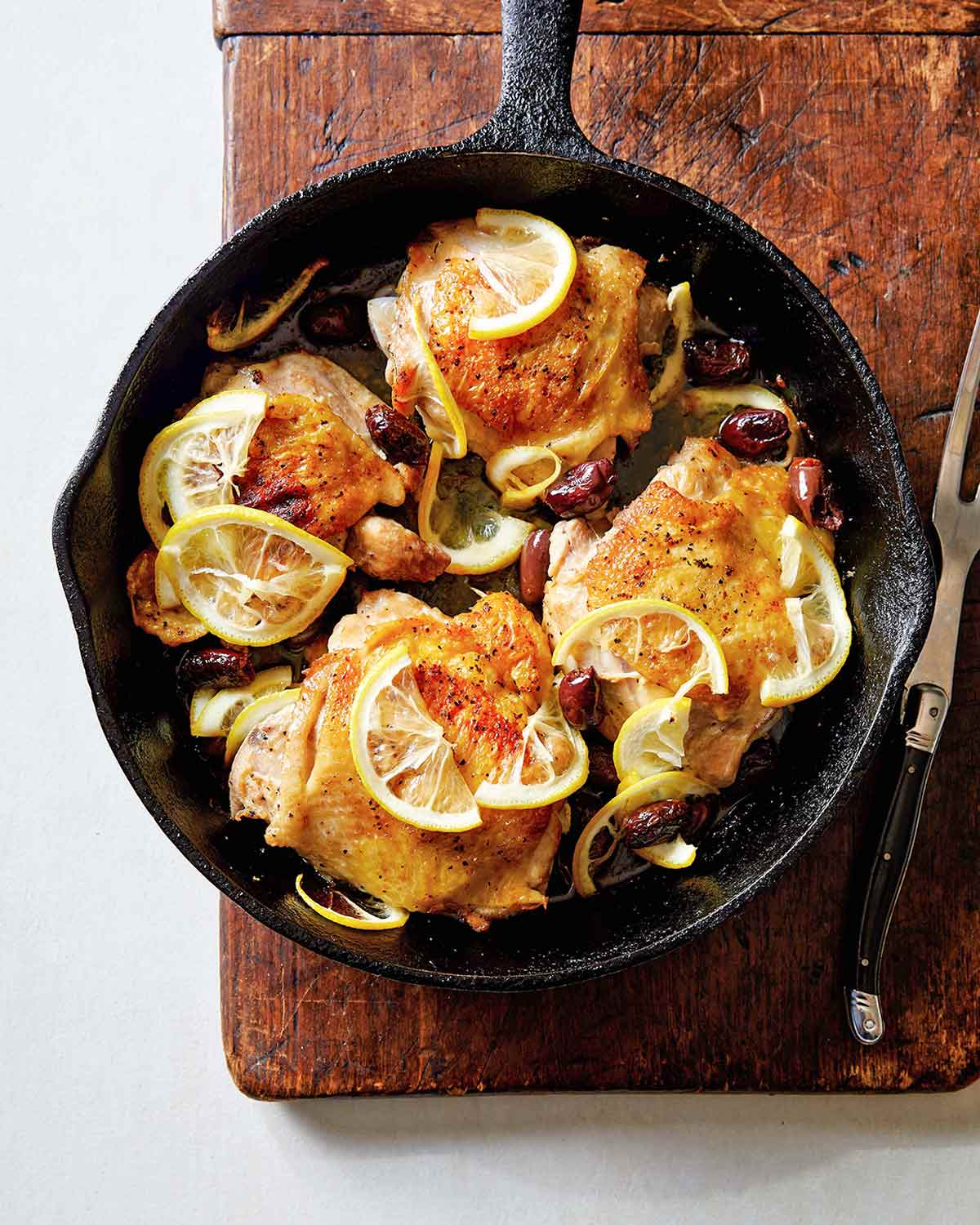 Four roast chicken thighs with lemon in a cast-iron skillet set on a wooden board with a meat fork resting beside it.