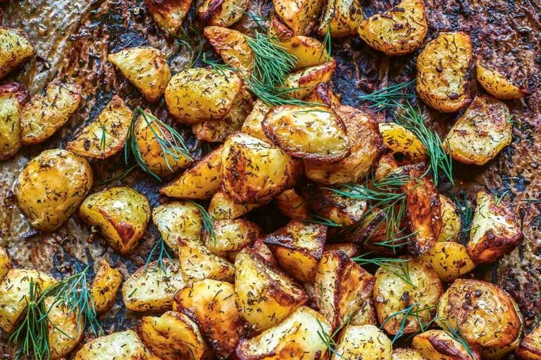 Roasted potatoes with dill on a baking sheet.