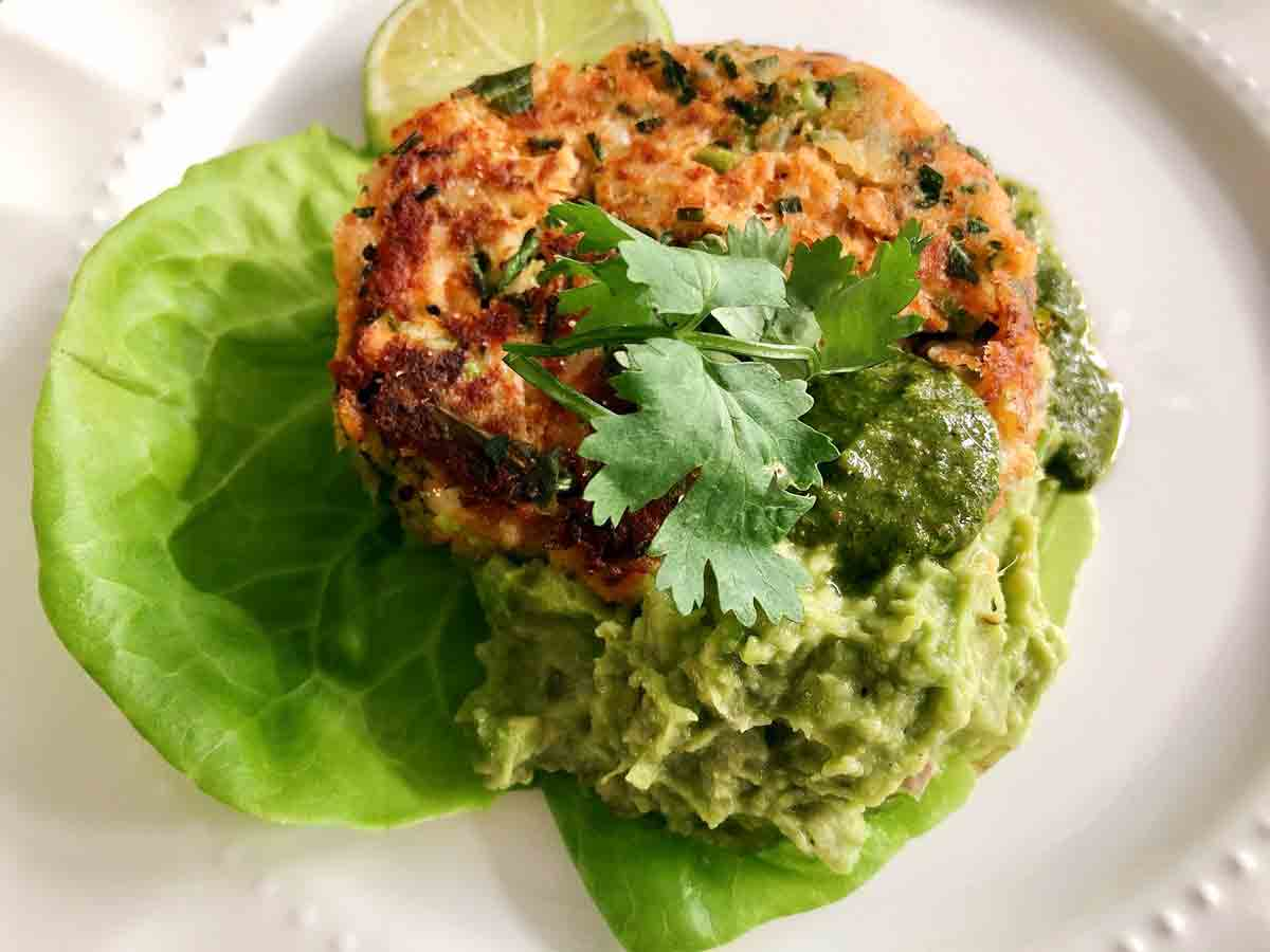 A salmon cake with a scoop of avocado spread, a drizzle of chimichurri, and a garnish of cilantro on a butter lettuce leaf.
