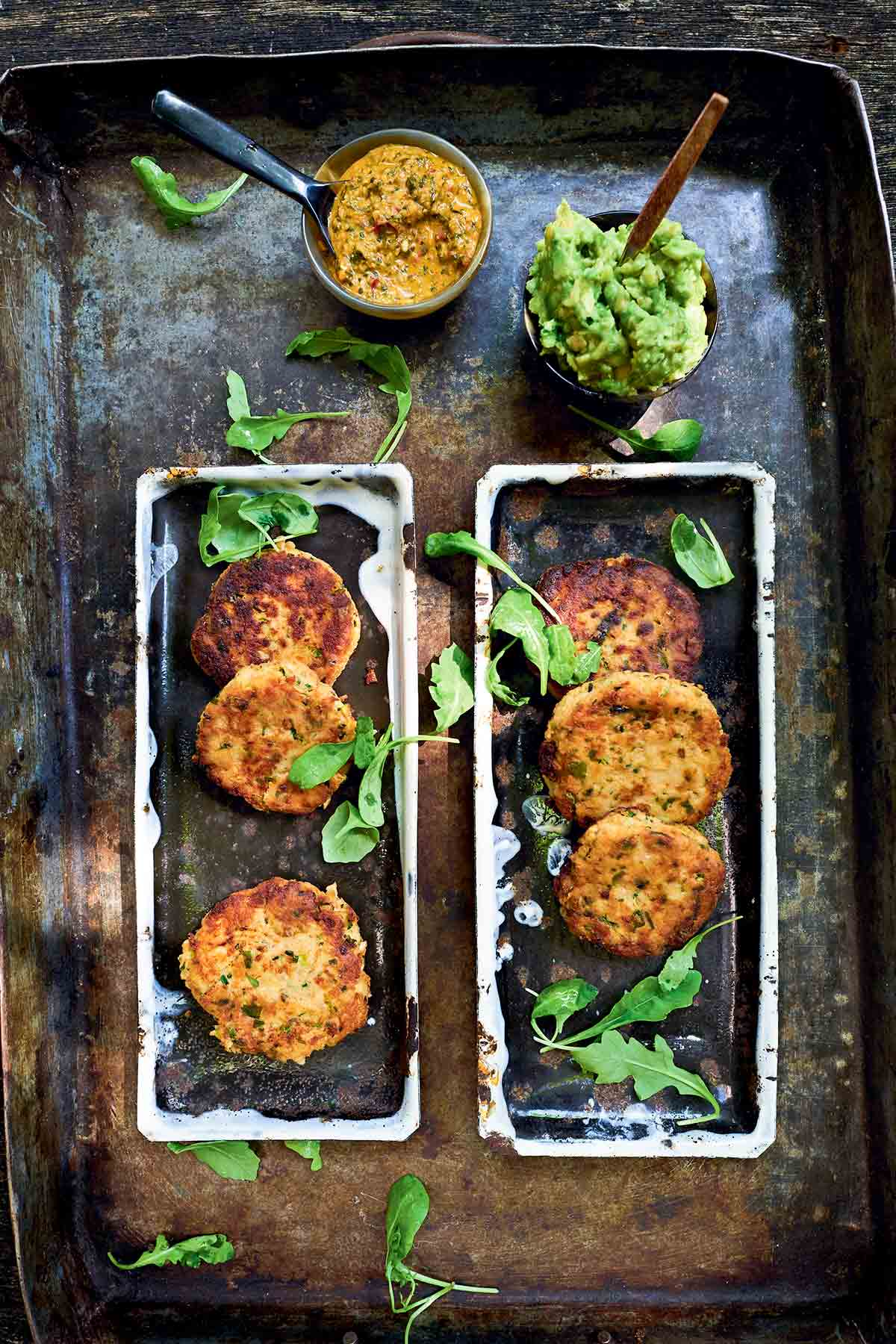 Six salmon cakes on rectangular platters with bowls of avocado spread and chimichurri beside.