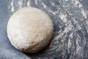 A ball of semolina pizza dough on a floured surface.