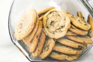 A glass jar filled with soft chocolate chip cookies.