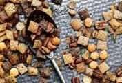 Spicy Chex mix scattered on a baking sheet with a spoon lying in the middle.