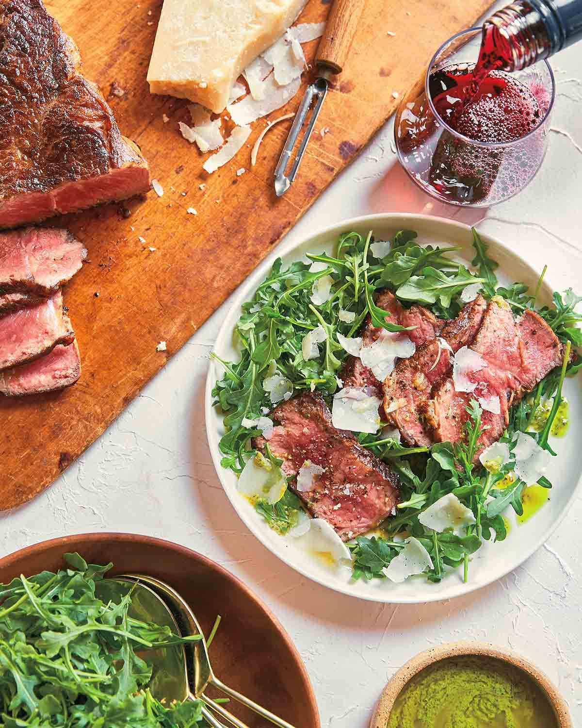 A steak and arugula salad with pesto vinaigrette in a white bowl, with a wooden board and sliced steak next to it.