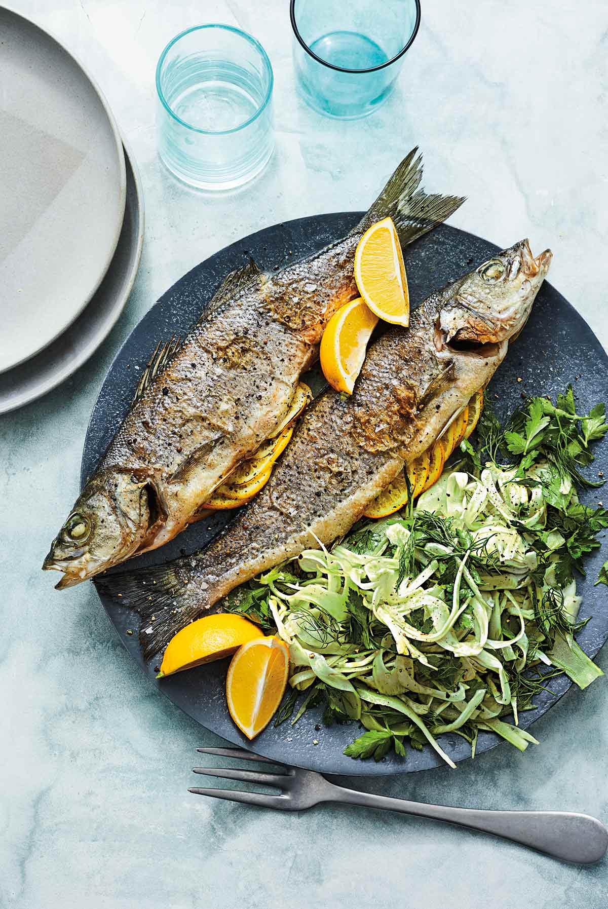 Two whole roasted branzino with lemon and shaved fennel salad on a blue plate with a fork, two glasses, and two grey plates beside it.