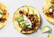 Four ancho pork and potato tacos topped with cubed pork and potatoes, sliced radish, sour cream, and cilantro.