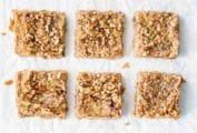 Six apple crumb bars on a white sheet.