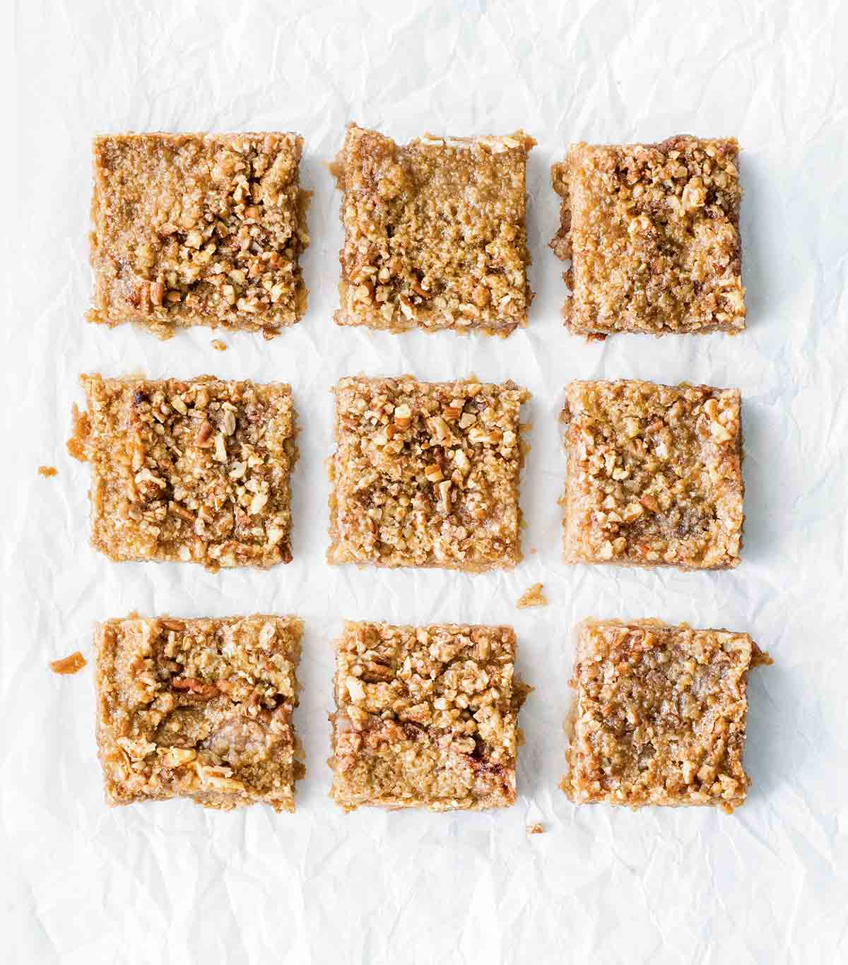 Nine apple crumb bars on a white sheet.