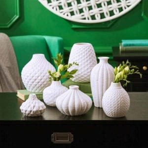Artisan Carvings Set of 7 Vases with green wall behind them.