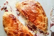 A halved round of baked Bried stuffed with cranberries in a puff pastry shell.