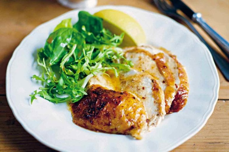 Plate of slices of baked chicken drizzled with cinnamon butter, green salad, and lemon wedge