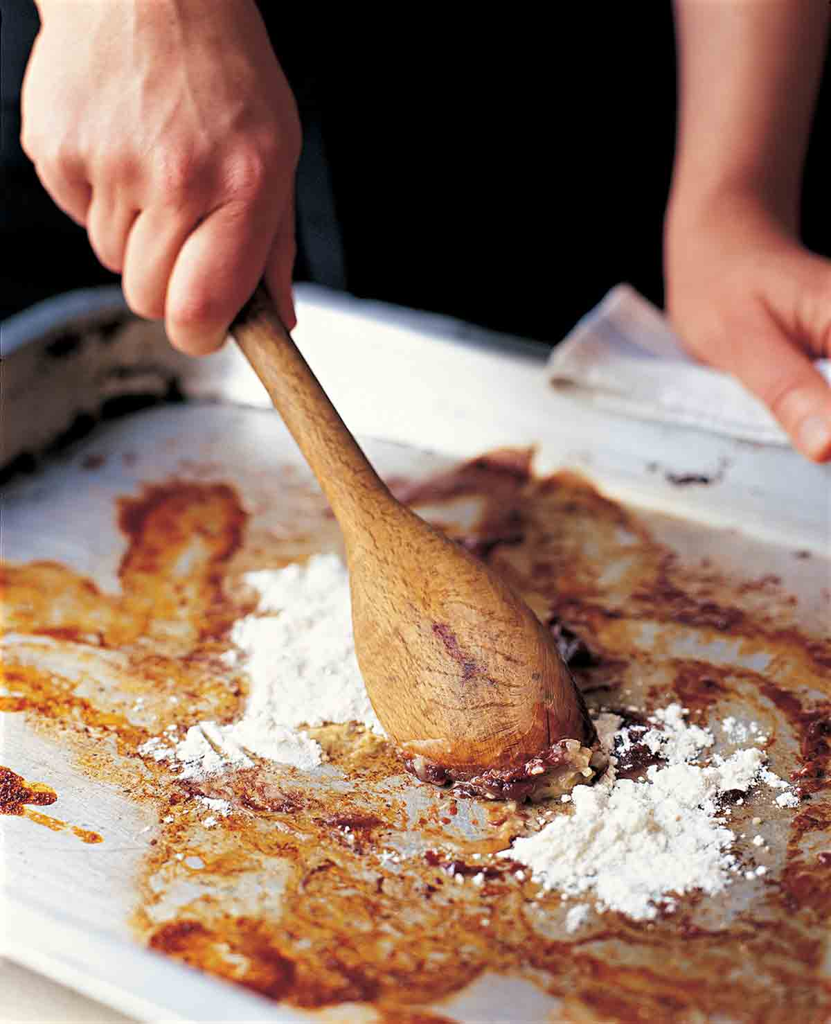 A person stirring flour into the basic pan gravy with a wooden spoon on a rimmed baking sheet.