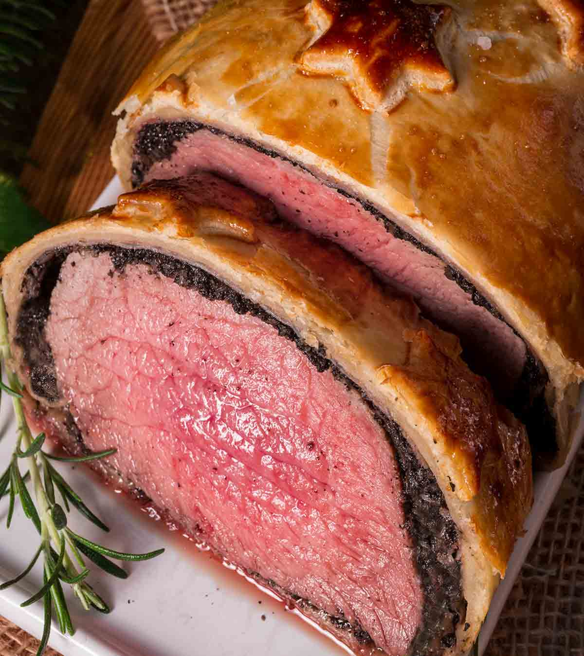 Close-up of a beef Wellington on a plate with a sprig of rosemary