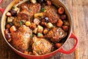 A red Dutch oven filled with beer-braised chicken with root vegetables on a wooden surface.