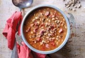 Bowl of black-eyed peas in a tomato broth on a sheet of wood