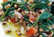 A white plate with black-eyed peas, spinach, red onion, and red pepper