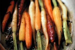 Assorted colors of braised carrots with orange and rosemary in a dish.