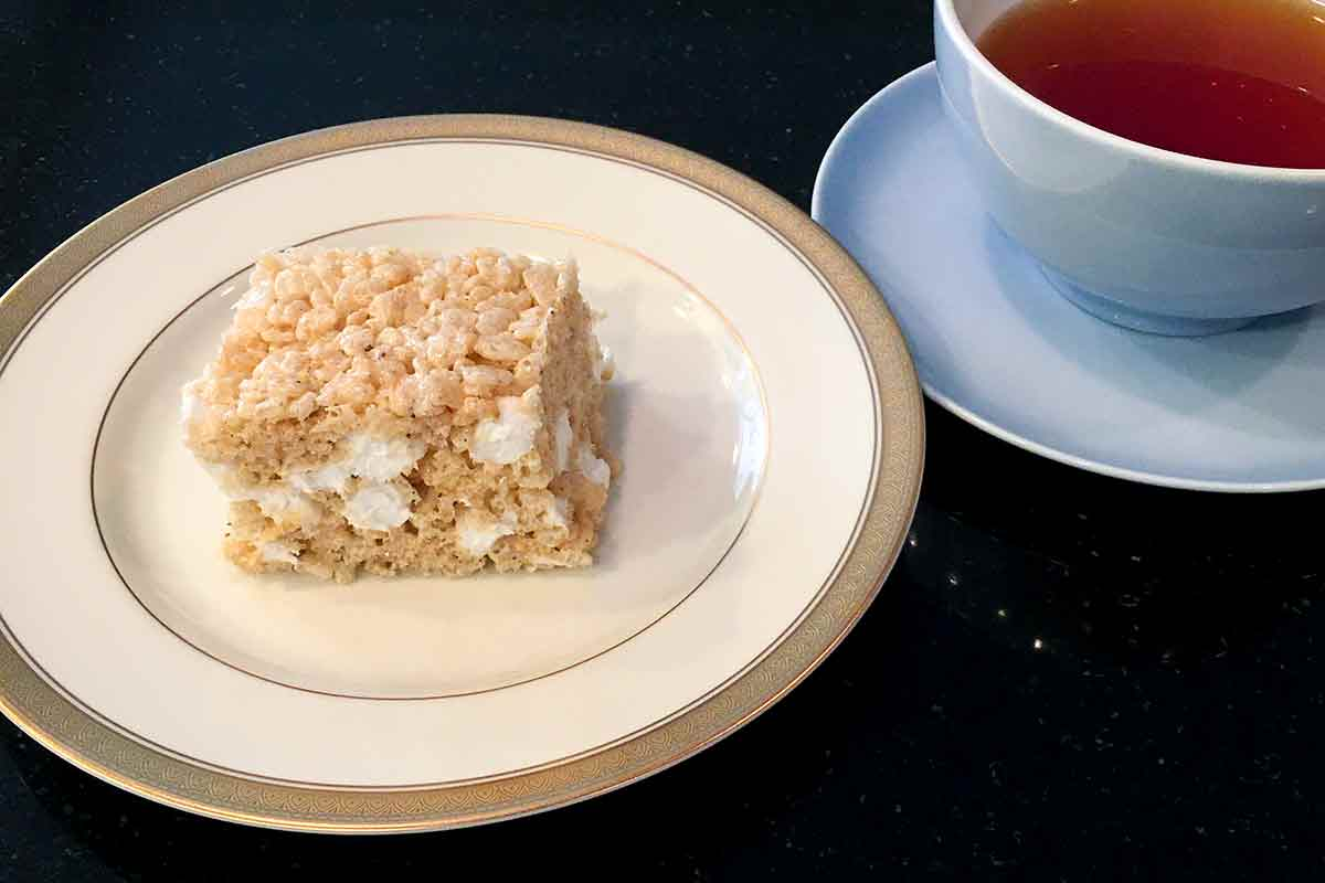 A brown butter rice Krispies treat on a china plate next to a cup of tea.