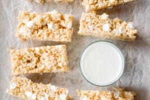 Nine brown butter rice krispies treats next to a glass of milk.