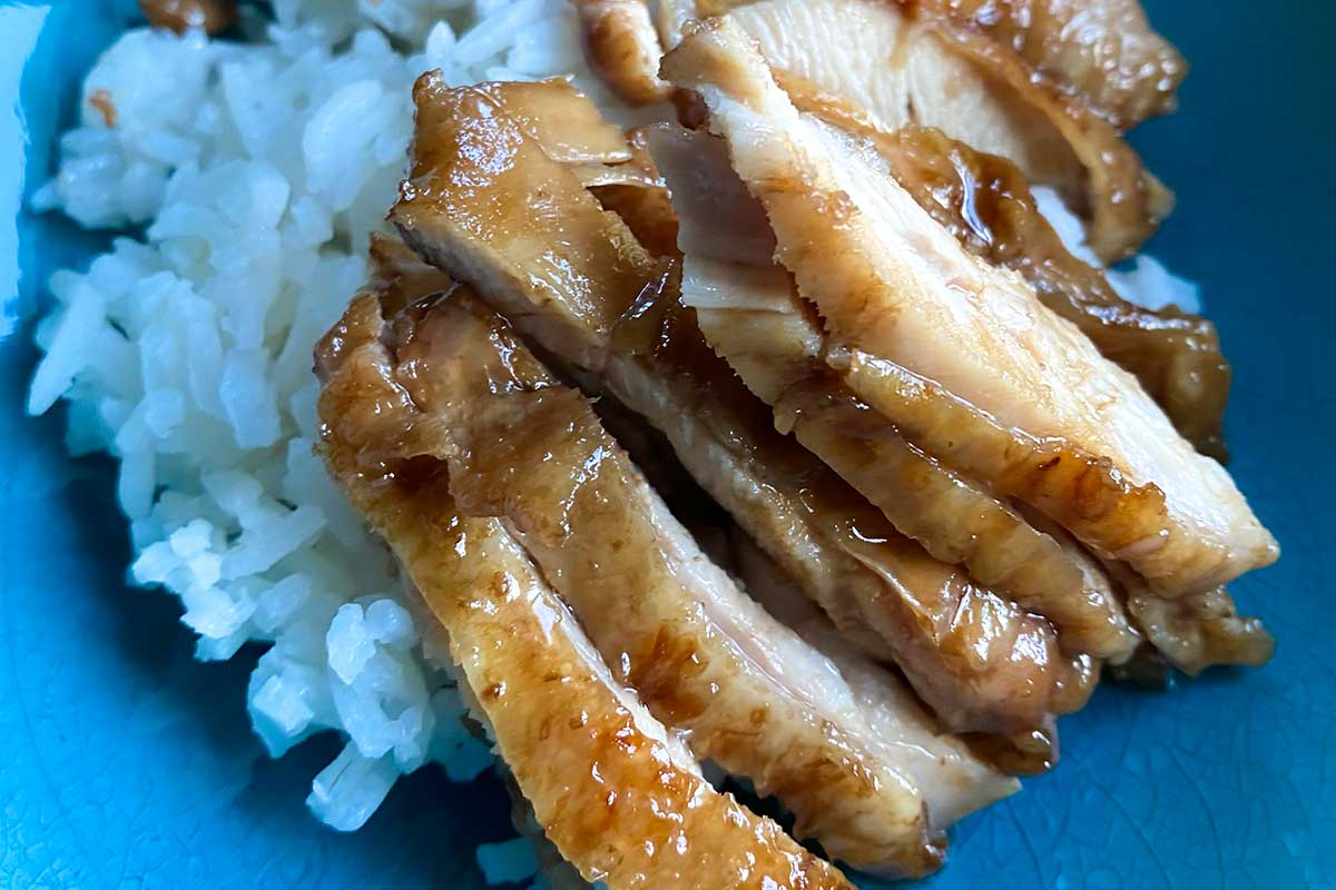 Chicken with teriyaki sauce on a white rice in a blue bowl.