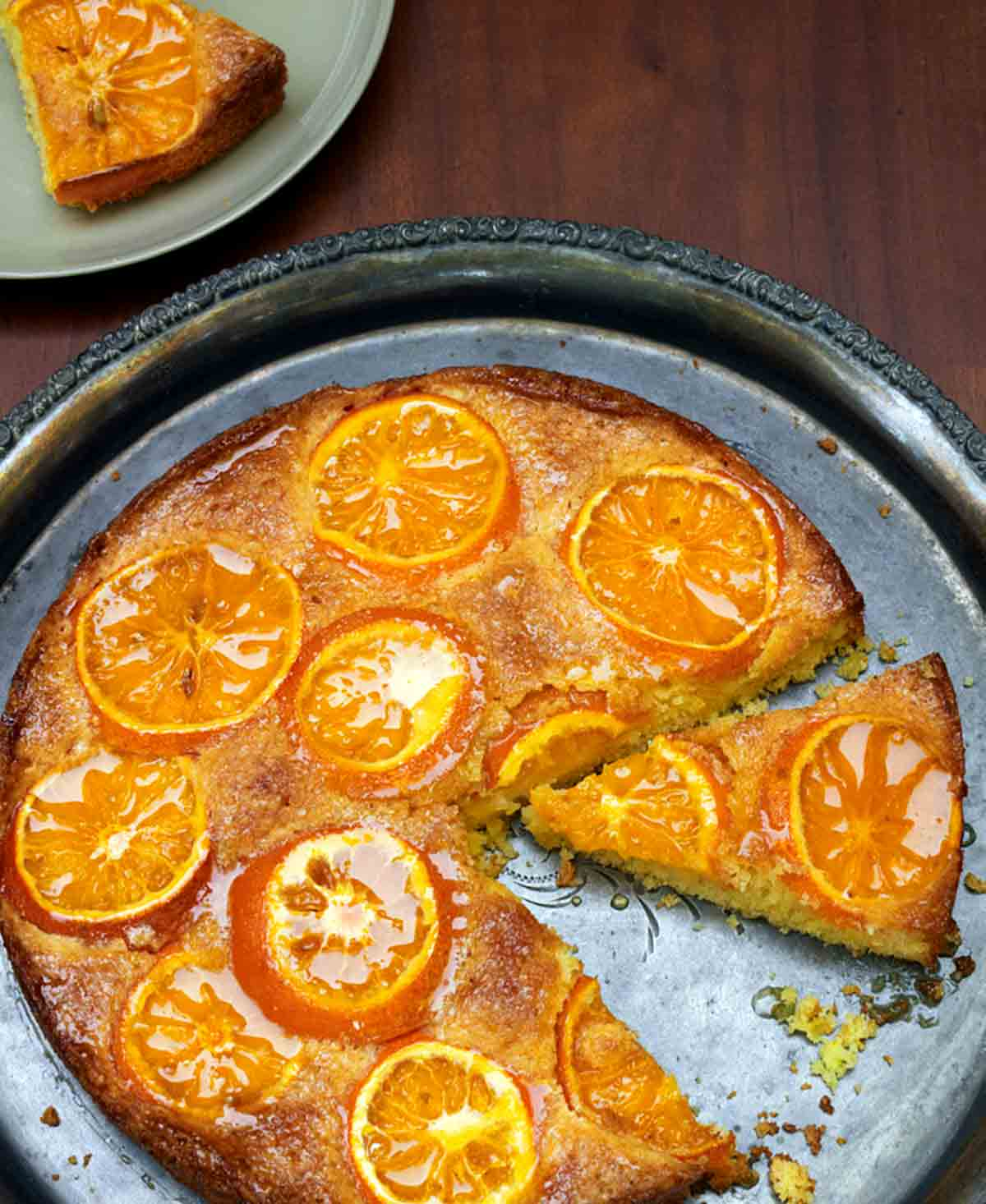 A clementine cake on a round silver platter with one slice on a plate beside it.