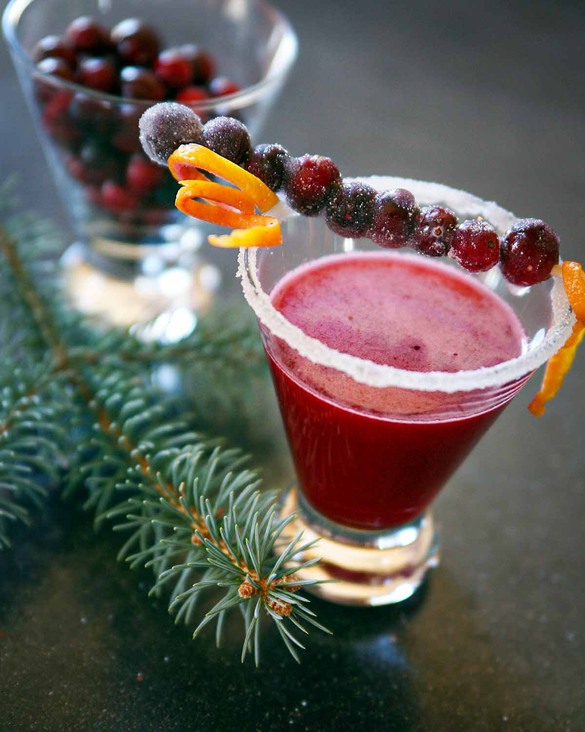 A cranberry margarita in a short glass with a skewer or sugared cranberries and orange zest across the top.