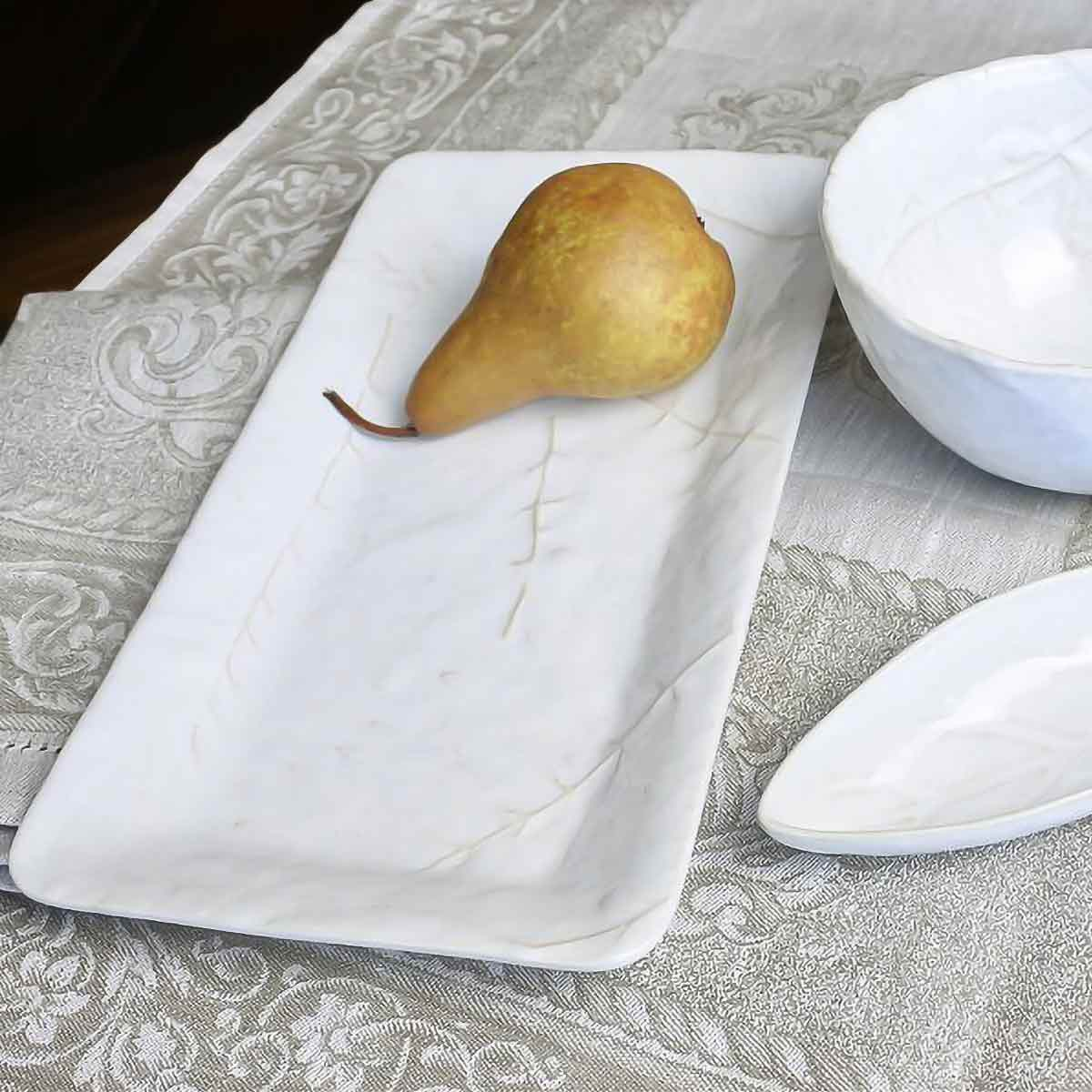 Didonato Floral Linen Table Runner shown with pear on white platter.