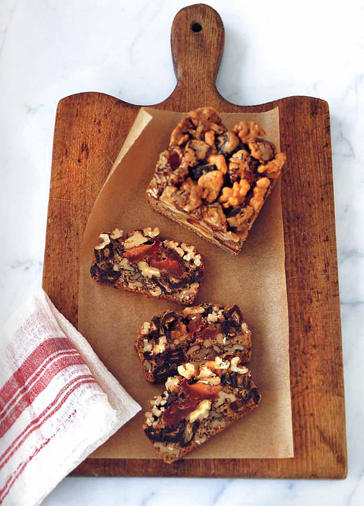 Dried fruit and nut cake cut into three slices on a cutting board on marble