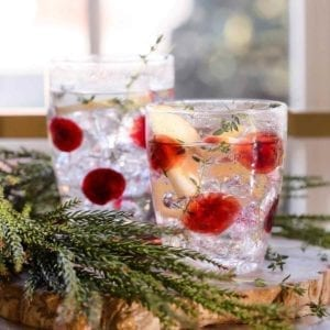Drop Glass Short Tumbler filled and garnished with thyme.