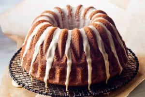 An espresso cake drizzled with glaze on a wire rack that is set on a pice of parchment to catch any glaze drips.