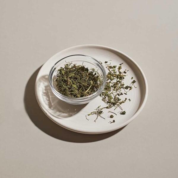 Fenugreek Leaves in glass ramekin on white plate.