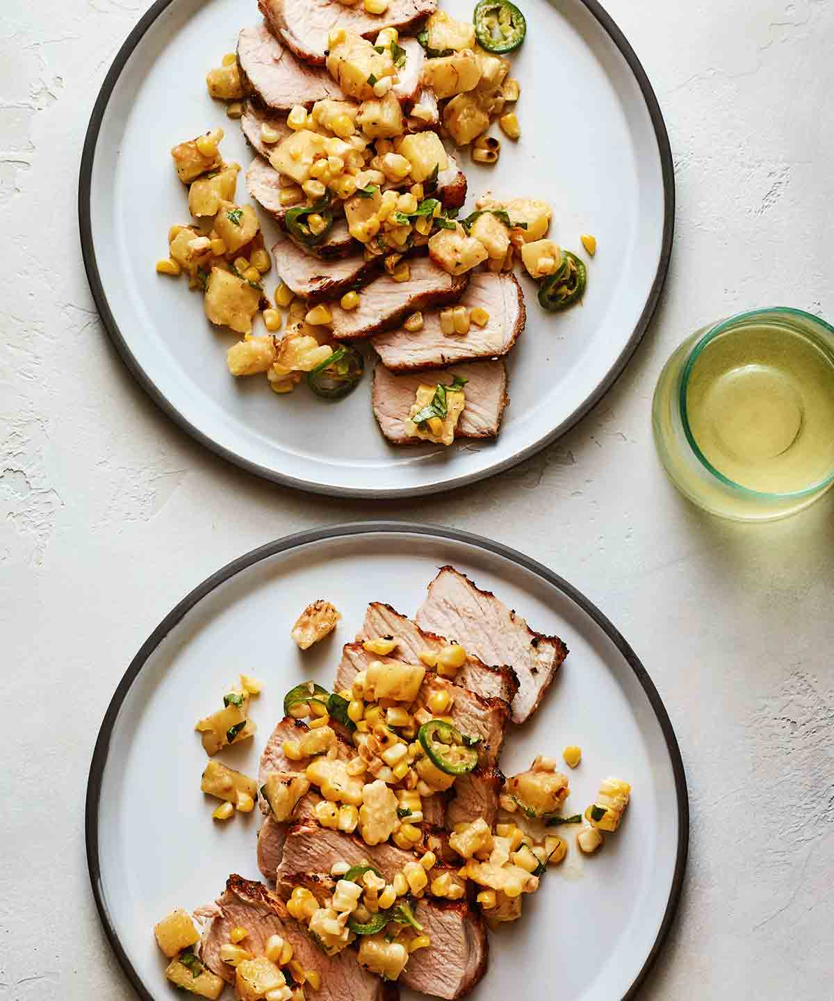 Two white plates topped with sliced grilled pork chops with pineapple and basil and corn and jalapeno.