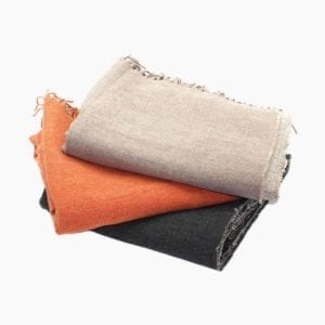 Harlow Henry Linen Merino Throw shown in taupe orange and black.