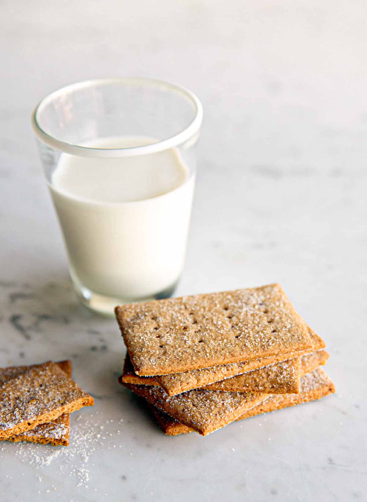 A pile of homemade graham crackers on a marble table with a glass of milk nearby