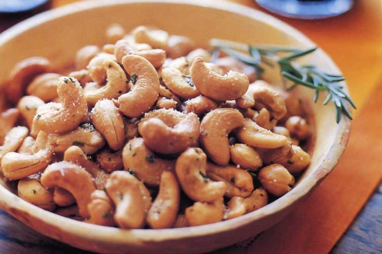 A bowl filled with Ina Garten's rosemary cashews with a sprig of rosemary on the side.