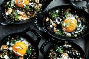 Mini Staub skillets filed with kale shakshuka--eggs, kale, and spices